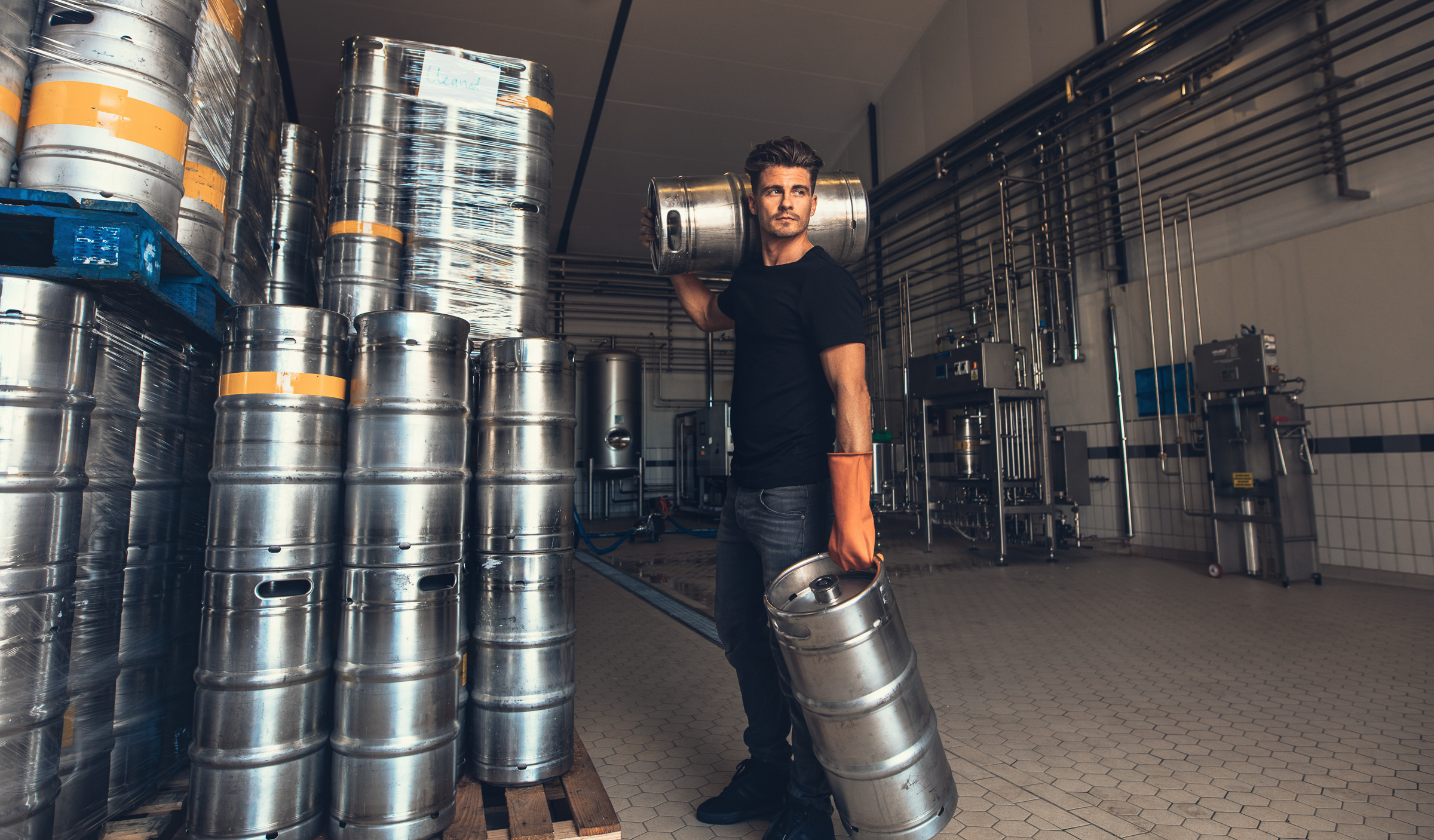 Young male brewer carrying keg at brewery factory. Young man with metal beer barrels at warehouse.