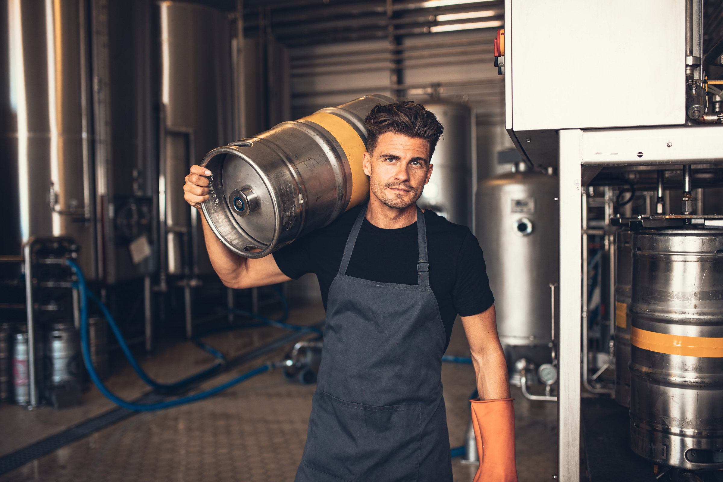 Portrait of male brewer carrying metal container at brewery factory. Young man holding a keg on shoulder at warehouse.