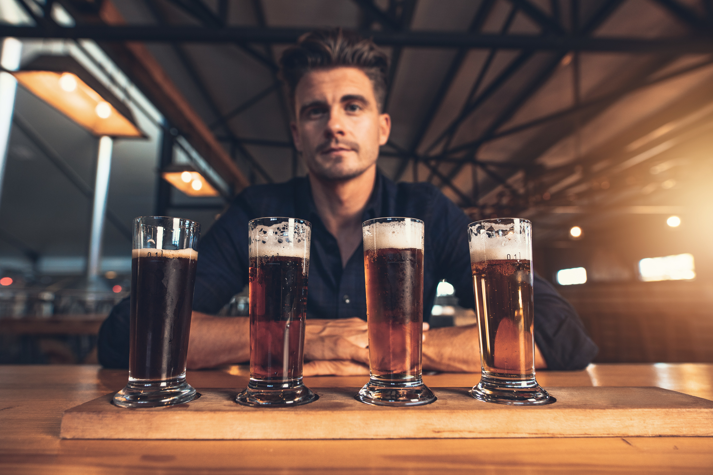 Young man tasting four different varieties of craft beer on a wooden table at brewery. Master brewer with four different types of beers at bar table.