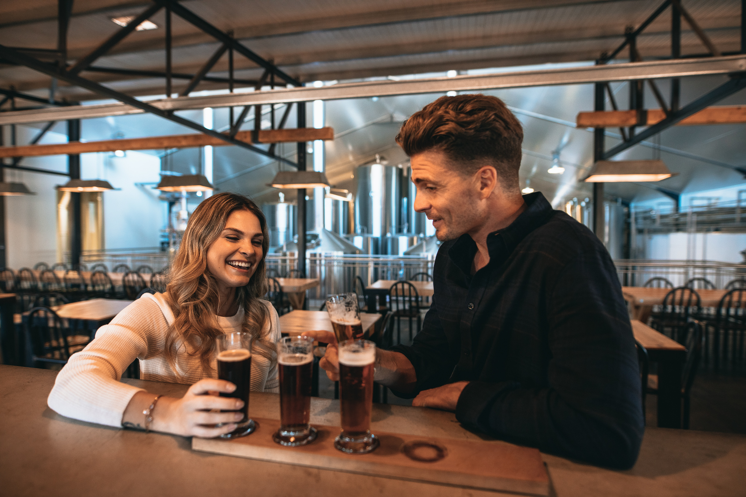 Happy young man and woman at brewery with selection of four different craft beers on table. Brewery owners tasting varieties of beers at the bar.