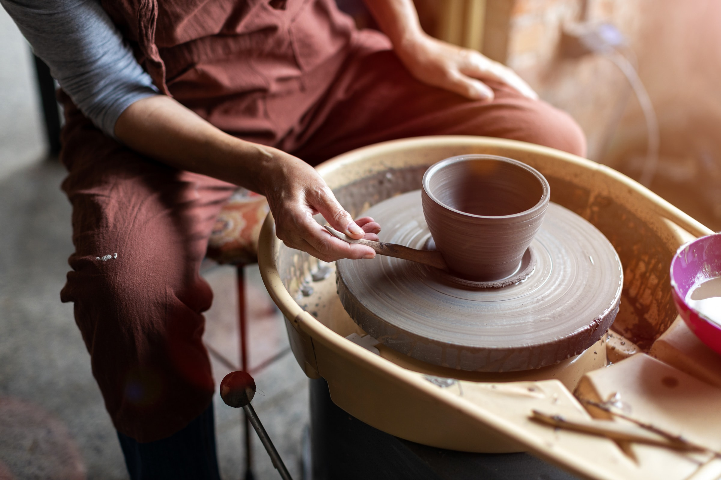 Hand made ceramics are formed by a mature woman business owner on a potters wheel