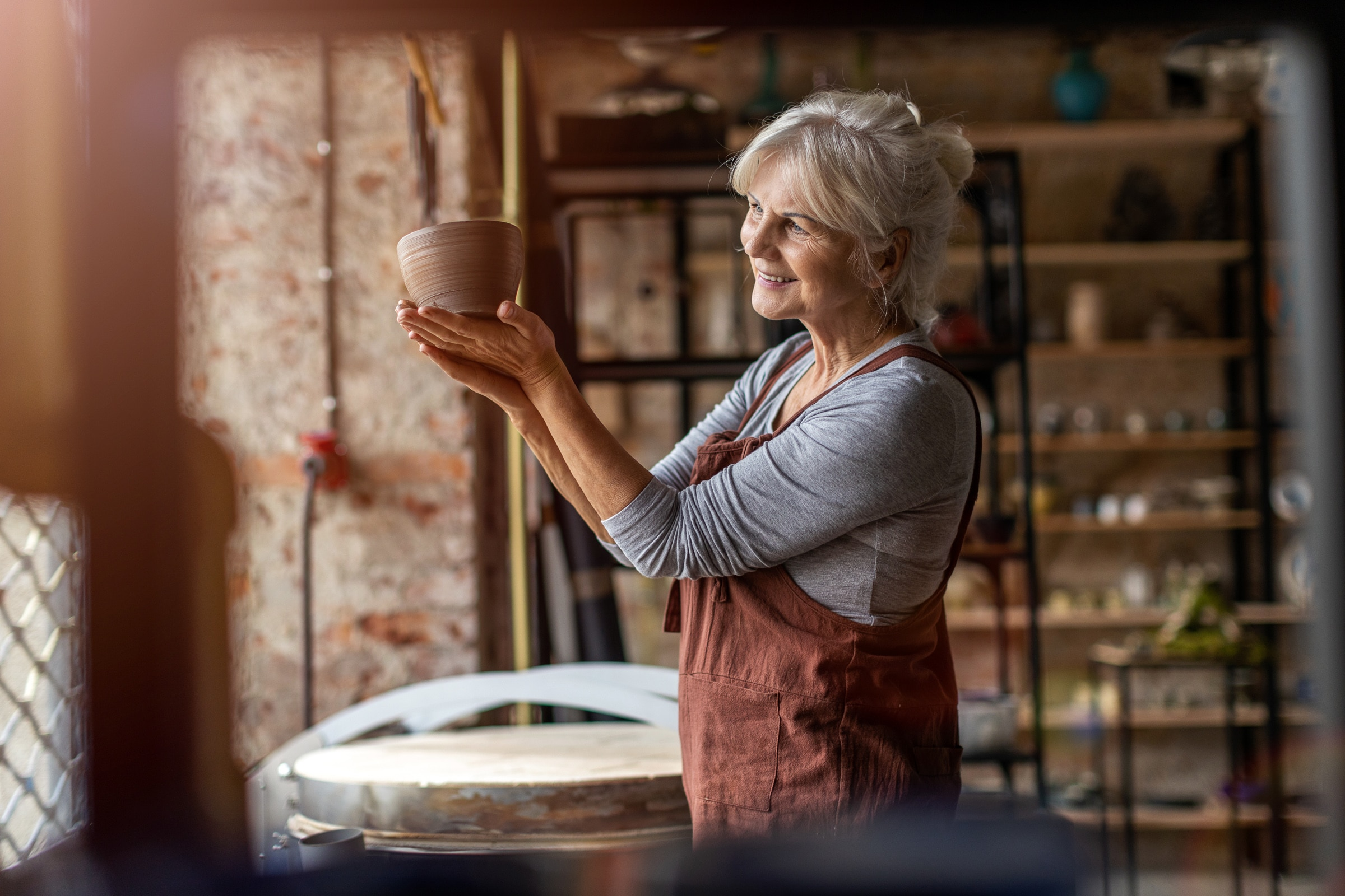 Smiling senior woman pottery artist business owner proudly looks a her ceramics from clay