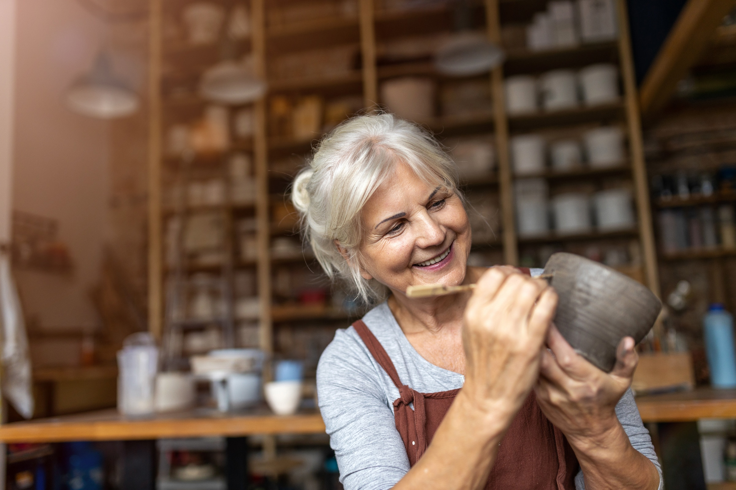 Smiling senior woman pottery artist business owner makes ceramics from clay