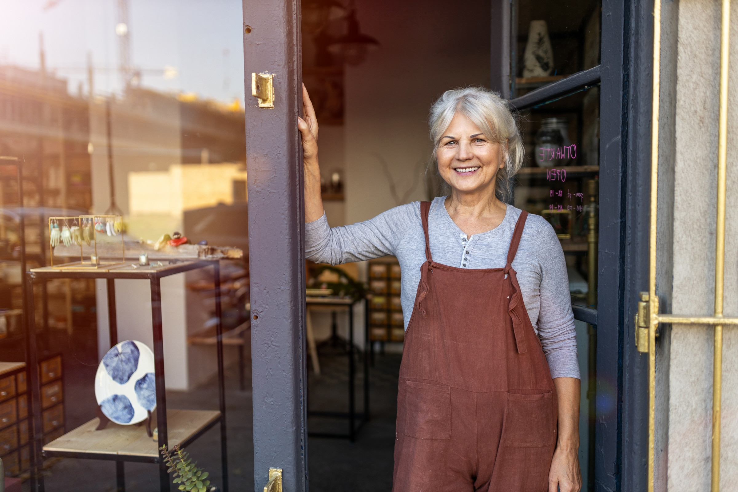 Portrait of smiling senior female pottery artist business owner in the doorway of her art studio