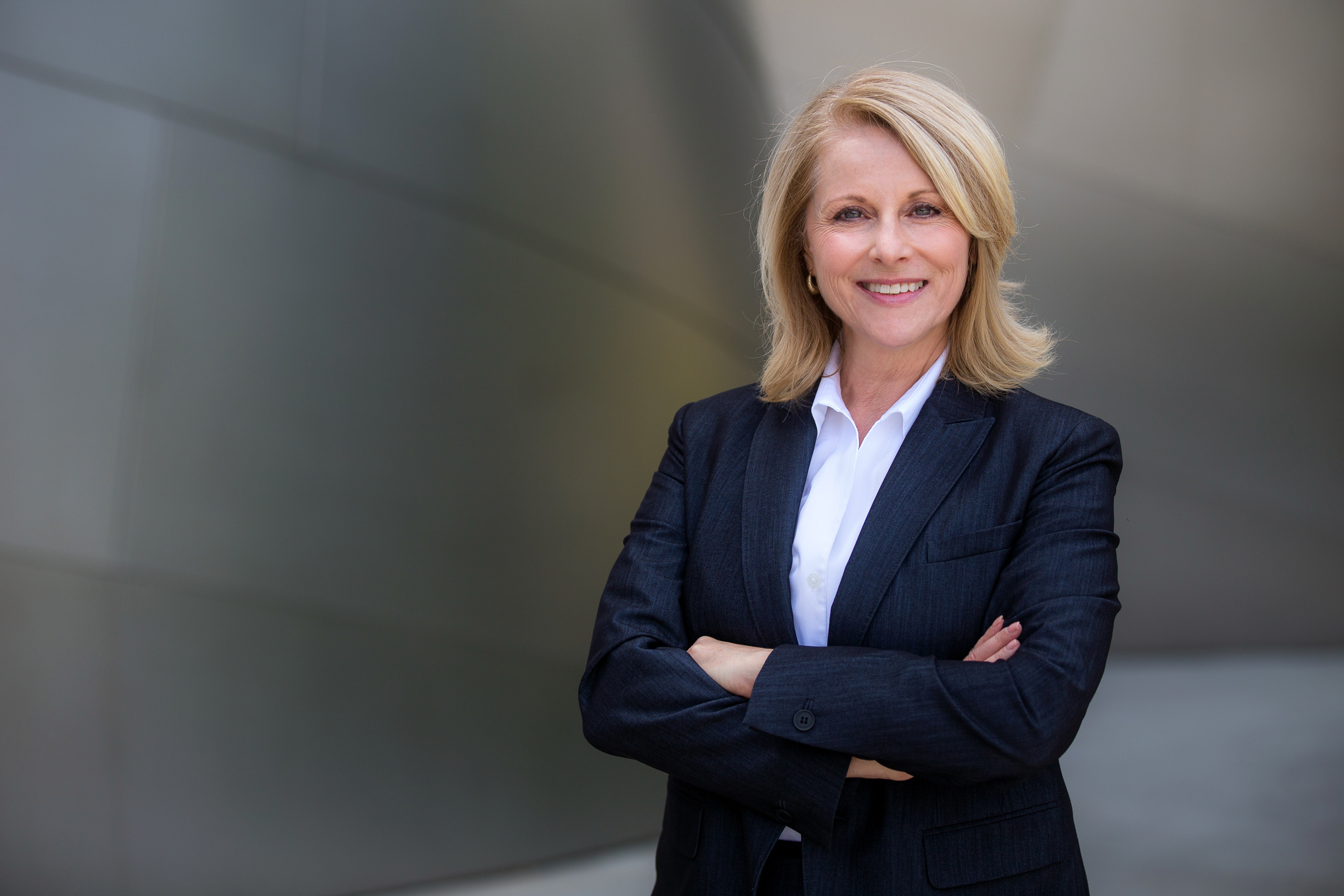 Pretty older business woman wearing blazer over white dress shirt, successful confidence with arms crossed and smiling