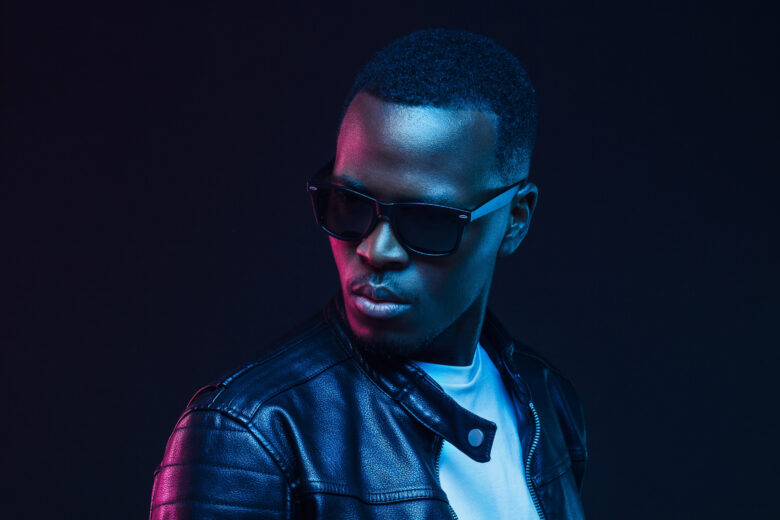 Close-up portrait of stylish black young man, wearing leather jacket and sunglasses in professional photography studio