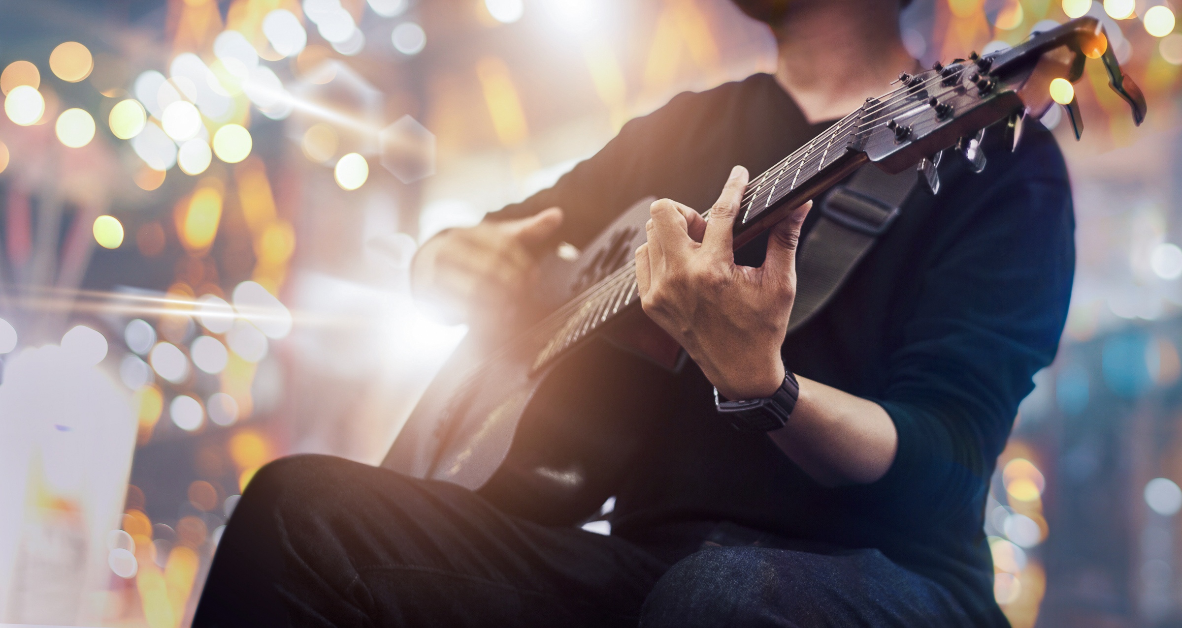Guitarist on stage and sings at a concert for background, soft bokeh and blur
